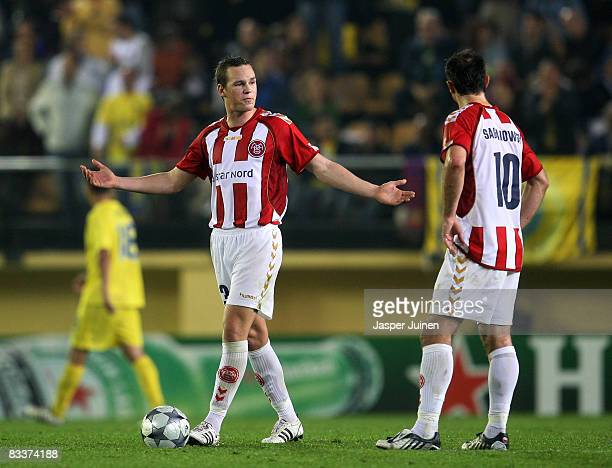Martin Pedersen of Aalborg reacts flanked by his teammate Marek Saganowski after conceding a goal during the UEFA Champions League Group E match...