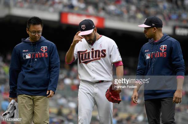 Martin Perez of the Minnesota Twins walks off the field after being hit by a ball that went for a single off the bat of Nicholas Castellanos of the...