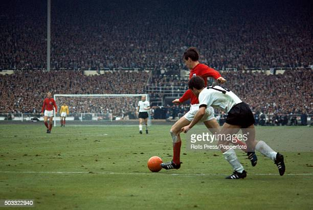 Martin Peters of England moves past Wolfgang Overath of West Germany during the FIFA World Cup Final between England and West Germany at Wembley...