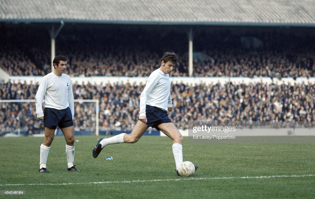 Martin Peters of Tottenham Hotspur (right) takes a free kick against Stoke City, watched by Alan Mullery (left), during their Division One football match at White Hart Lane in London, on 25th October 1971. Tottenham Hotspur won 3-0.