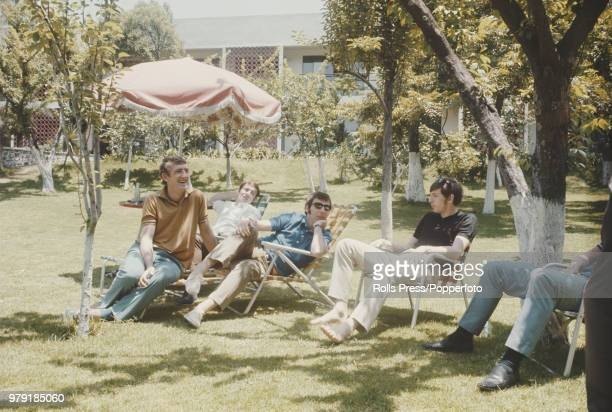 Martin Peters sits with from left Alex Stepney Ralph Coates and David Sadler of the England national football team squad as they relax in the grounds...