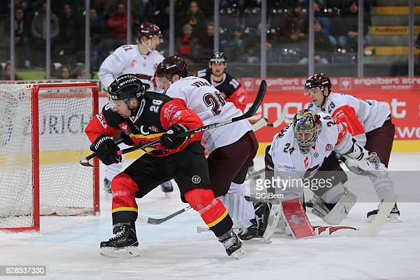 Martin Pluess of Bern challenges goalkeeper Tomas Pollerle and the defense of Prague during the Champions Hockey League Quarter Final match between...