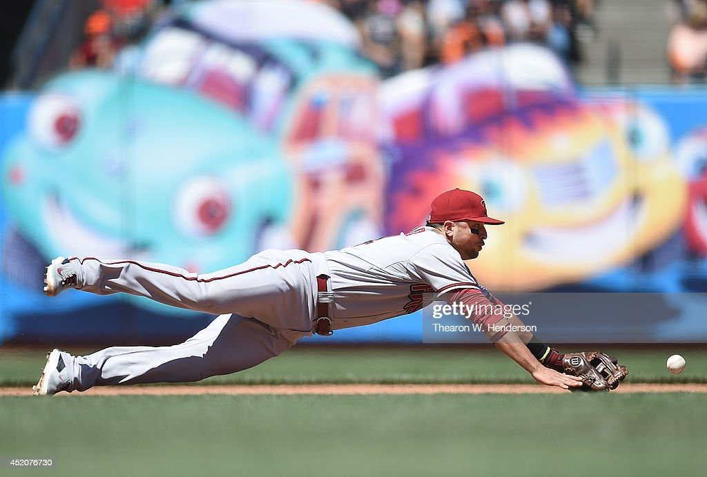 Martin Prado #14 of the Arizona Diamondbacks dives for this ball that goes for a base hit off the bat of Joaquin Arias #13 of the San Francisco Giants in the bottom of the seventh inning at AT&T Park on July 12, 2014 in San Francisco, California.