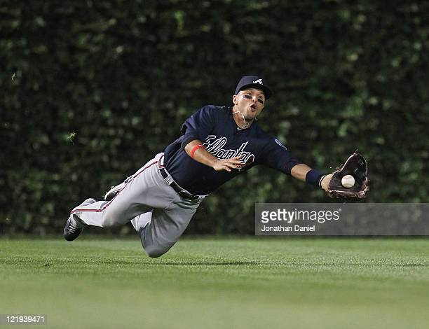 Martin Prado of the Atlanta Braves dives to make a catch on a ball hit by Alfonso Soriano of the Chicago Cubs at Wrigley Field on August 23 2011 in...
