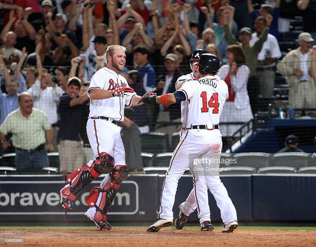 Martin Prado #14 of the Atlanta Braves is congratulated by Chipper Jones #10 and Brian McCann #16 after scoring the game-winning run against the Cincinnati Reds at Turner Field on May 19, 2010 in Atlanta, Georgia. The Braves defeated the Reds 5-4.