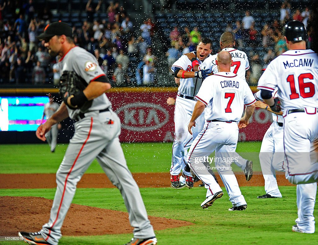 Martin Prado #14 of the Atlanta Braves is mobbed by teammates after knocking in the game-winning run in the 11th inning against the San Francisco Giants at Turner Field on August 16, 2011 in Atlanta, Georgia.