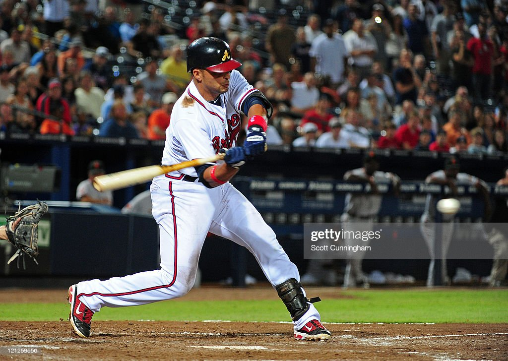 Martin Prado #14 of the Atlanta Braves singles in the 11th inning to knock in the game-winning run against the San Francisco Giants at Turner Field on August 16, 2011 in Atlanta, Georgia.