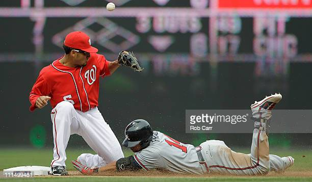 Martin Prado of the Atlanta Braves slides safely into second base for a double as shortstop Ian Desmond of the Washington Nationals bobbles the throw...