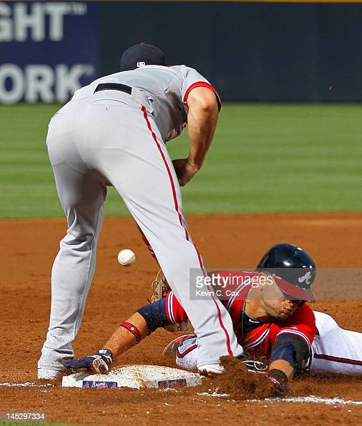 Martin Prado of the Atlanta Braves slides safely into third base under Ryan Zimmerman of the Washington Nationals in the third inning at Turner Field...