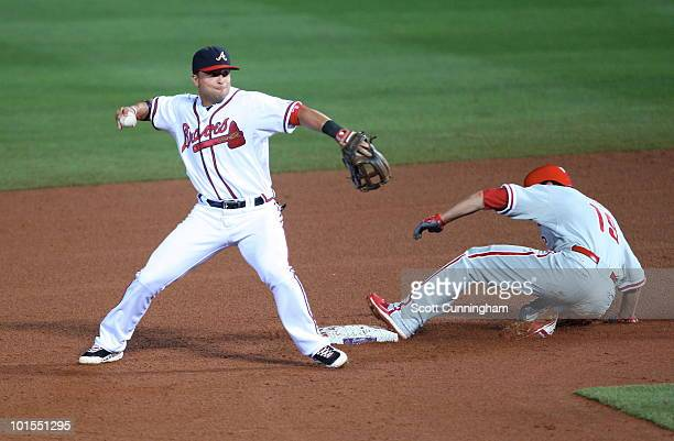 Martin Prado of the Atlanta Braves turns a double play against Greg Dobbs of the Philadelphia Phillies at Turner Field on June 1 2010 in Atlanta...