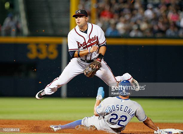 Martin Prado of the Atlanta Braves turns a double play over Scott Podsednik of the Kansas City Royals in the ninth inning at Turner Field on June 19...