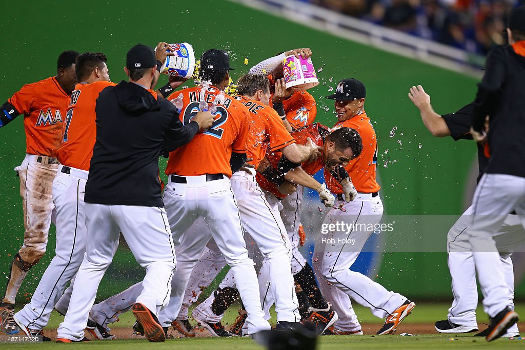 Martin Prado #14 of the Miami Marlins celebrates with teammates after hitting a walk-off sacrifice fly ball to end the game against the New York Mets at Marlins Park on September 6, 2015 in Miami, Florida. The Marlins beat the Mets by a score of 4-3 in nine innings.
