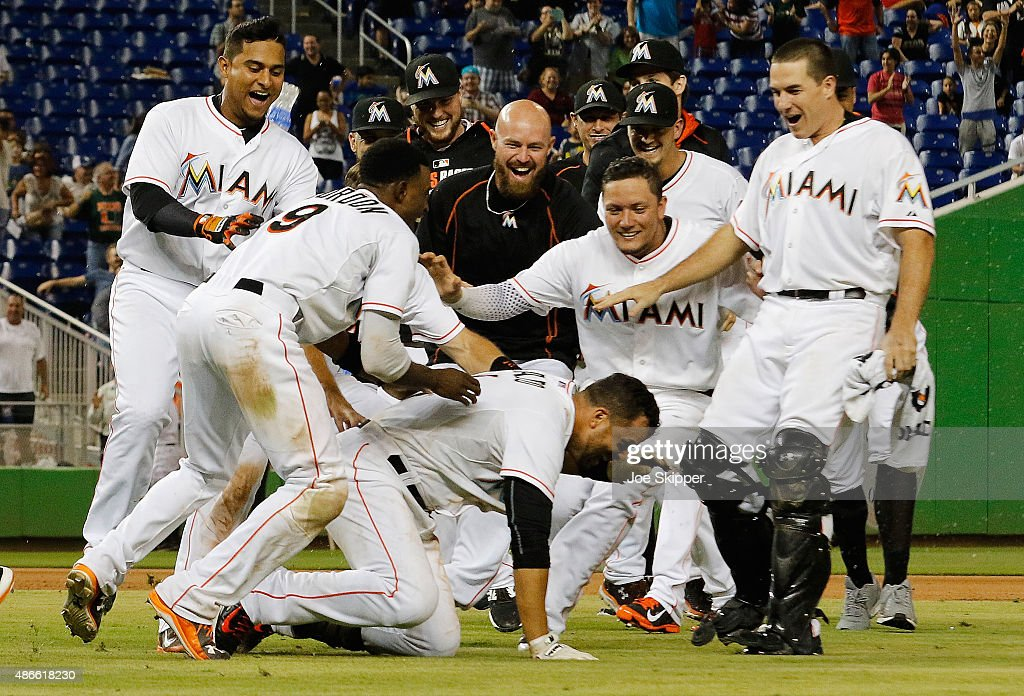 Martin Prado #14 of the Miami Marlins (below) is mobbed by teammates after his game-winning walk-off hit in the 11th inning to defeat the New York Mets 6-5 at Marlins Park on September 4, 2015 in Miami, Florida.
