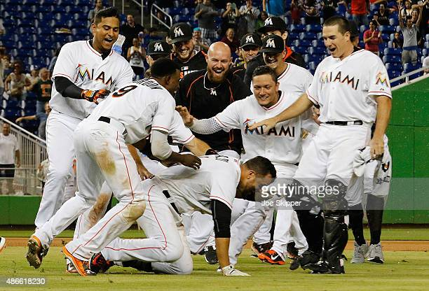Martin Prado of the Miami Marlins is mobbed by teammates after his game-winning walk-off hit in the 11th inning to defeat the New York Mets 6-5 at...