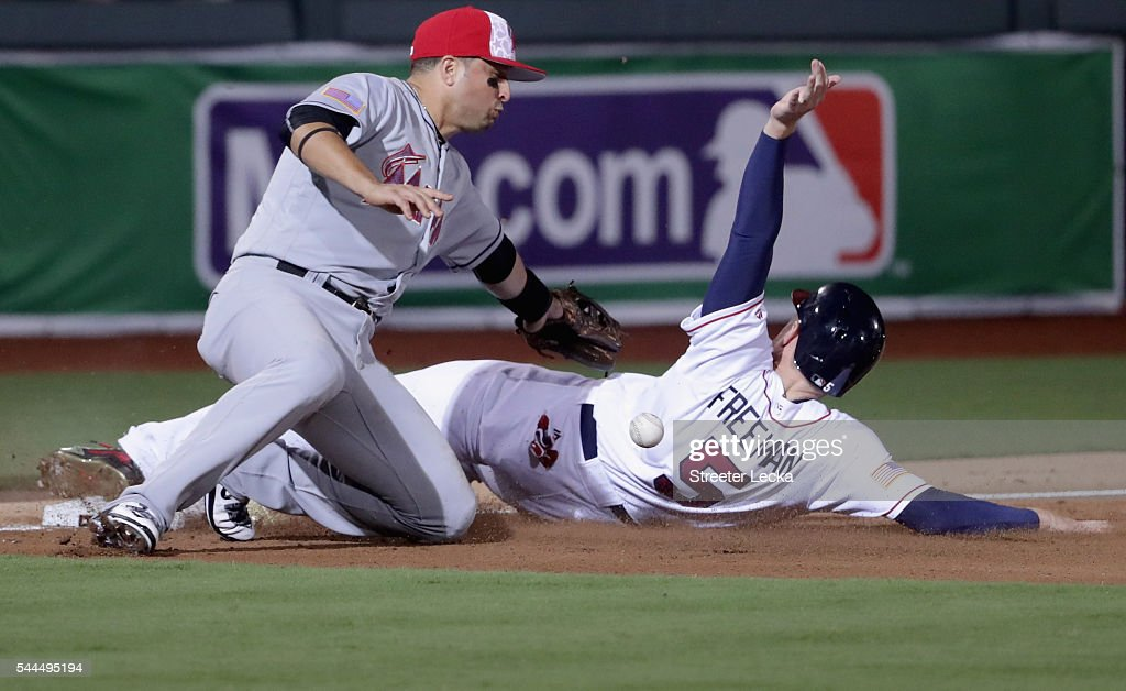 Martin Prado #14 of the Miami Marlins misses a tag at third base on Freddie Freeman #5 of the Atlanta Braves during their game at Fort Bragg Field on July 3, 2016 in Fort Bragg, North Carolina. The Fort Bragg Game marks the first regular season MLB game ever to be played on an active military base.