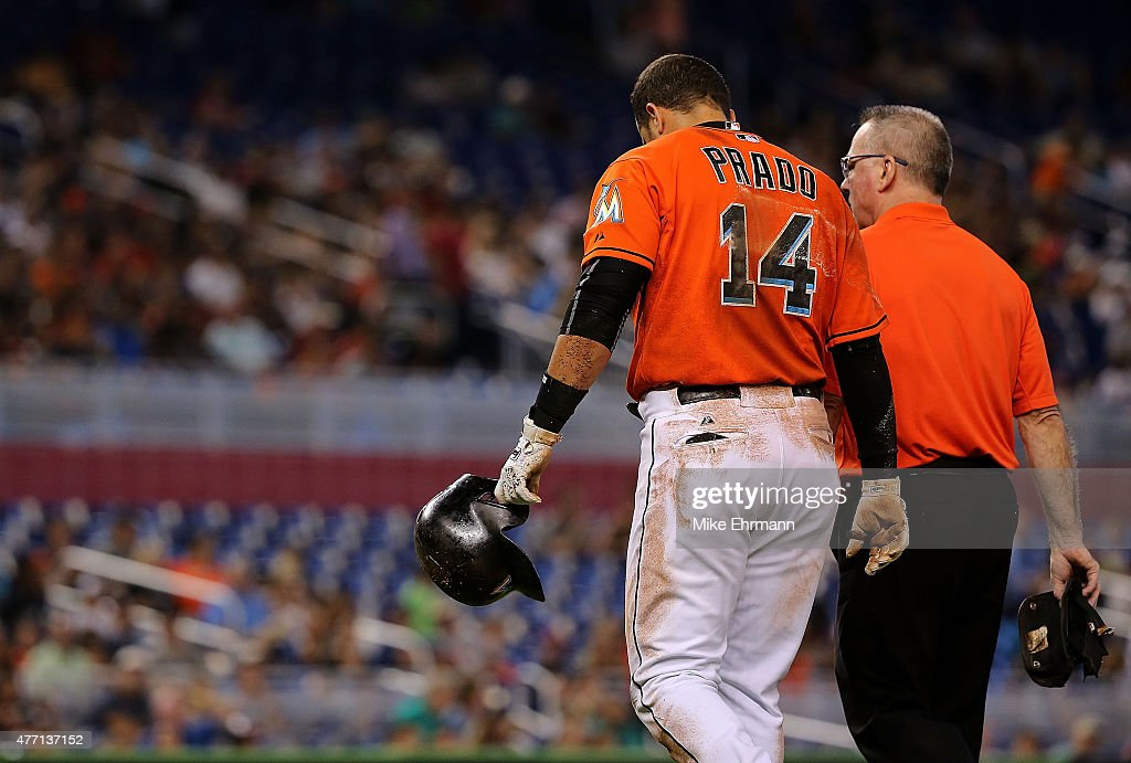 Martin Prado #14 of the Miami Marlins reacts to injuring his shoulder after falling crossing first base during a game against the Colorado Rockies at Marlins Park on June 14, 2015 in Miami, Florida.