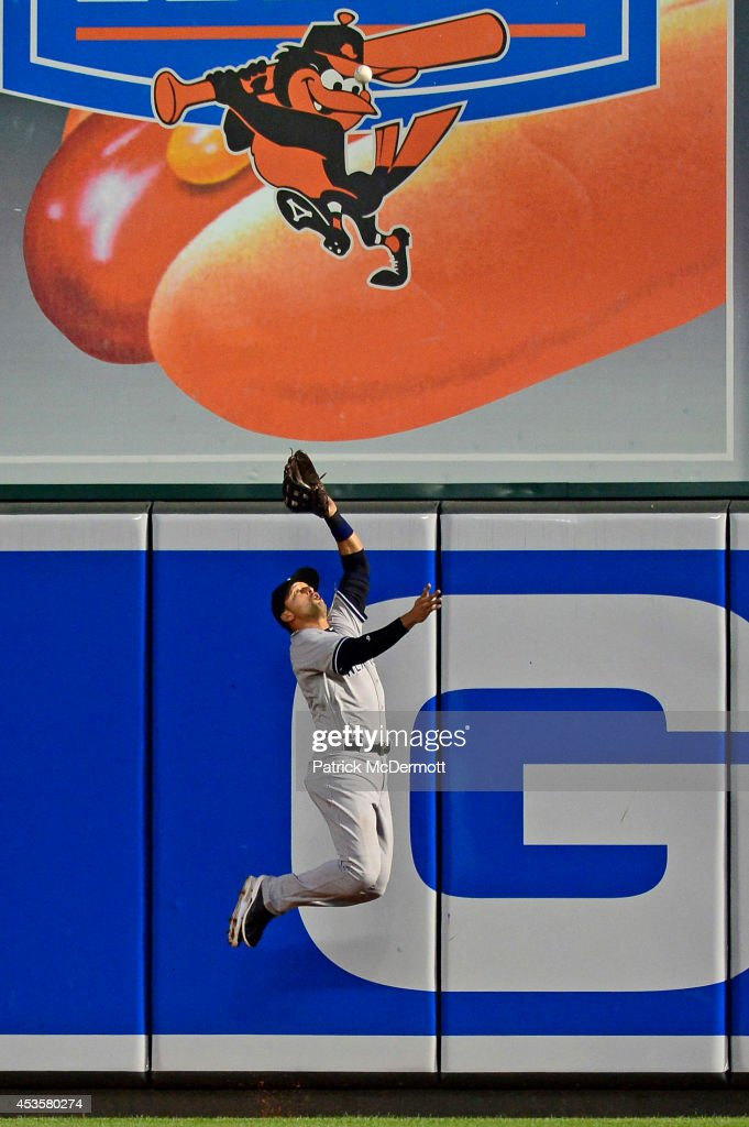 Martin Prado #14 of the New York Yankees catches a fly ball hit by Chris Davis #19 of the Baltimore Orioles (not pictured) in the fourth inning during a baseball game at Oriole Park at Camden Yards on August 13, 2014 in Baltimore, Maryland.