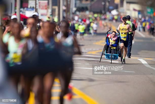 Martin Richard Foundation runner Matt Burdette pushed friend Kevin DiLegge during the 120th Boston Marathon on Monday April 18 2016 At left are the...