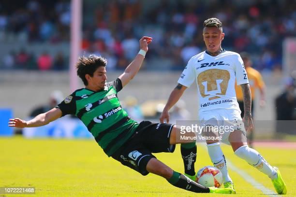 Martin Rodriguez of Pumas struggles for the ball against Carlos Orrantia of Santos during the 17th round match between Pumas UNAM vs Santos Laguna as...
