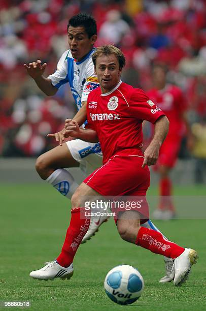 Martin Romagnoli of Toluca fights for the ball with Roberto Carlos Juarez of Puebla during a match as part of the 2010 Bicentenary Tournament in the...