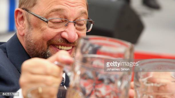 Martin Schulz chancellor candidate of the German Social Democrats cheers with beer mugs in a fest tent at the Gillamoos amusement fair on September 4...