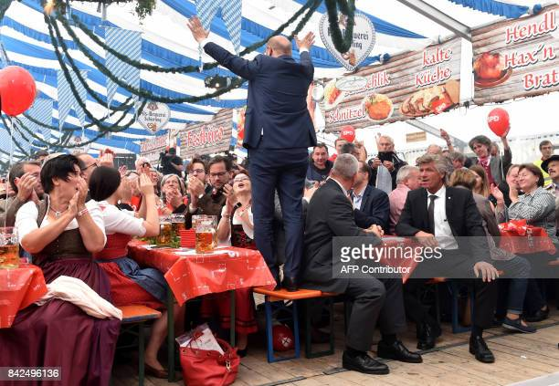 Martin Schulz leader of Germany's social democratic SPD party and candidate for Chancellor stands on a bench as he is applauded by supporters in a...