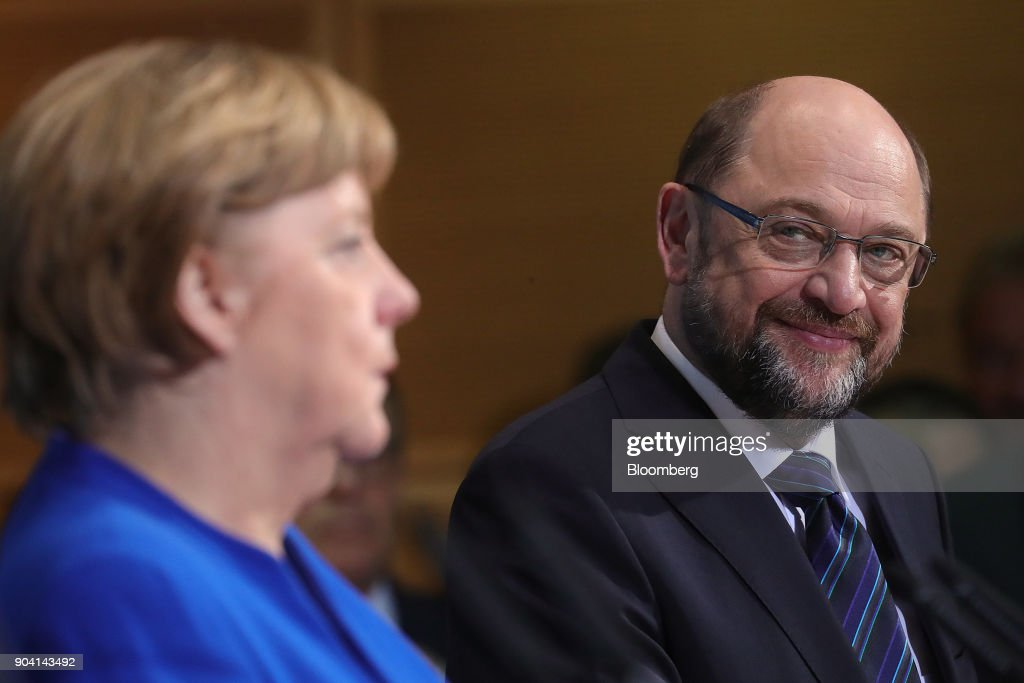 Martin Schulz, leader of the Social Democrat Party (SPD), right, looks towards Angela Merkel, Germany's chancellor, during a news conference following overnight coalition negotiations, at the SPD headquarters in Berlin, Germany, on Friday, Jan. 12, 2018. After a marathon of more than 24 hours of talks to end Germanys political gridlock, leaders of Merkels Christian Democratic Union, her Bavarian sister party and the Social Democrats hammered out a 28-page agreement. Photographer: Krisztian Bocsi/Bloomberg via Getty Images