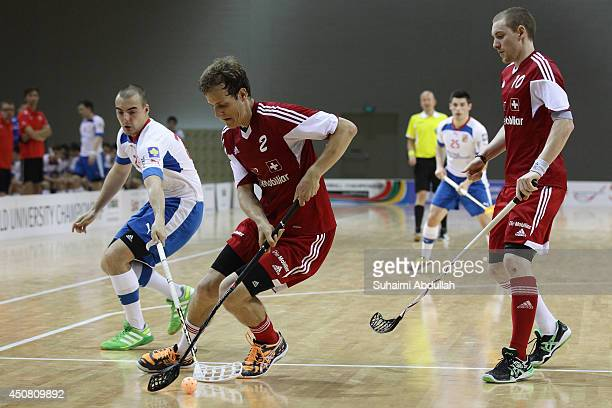 Martin Simek of Czech Republic vies for the ball with Bolliger Florian of Switzerland during the World University Championship Floorball match...