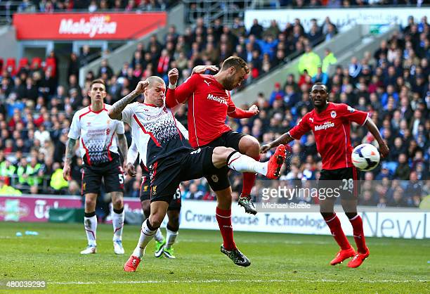 Martin Skrtel of Liverpool scores his team's second goal despite the challenge from during the Barclays Premier League match between Cardiff City and...