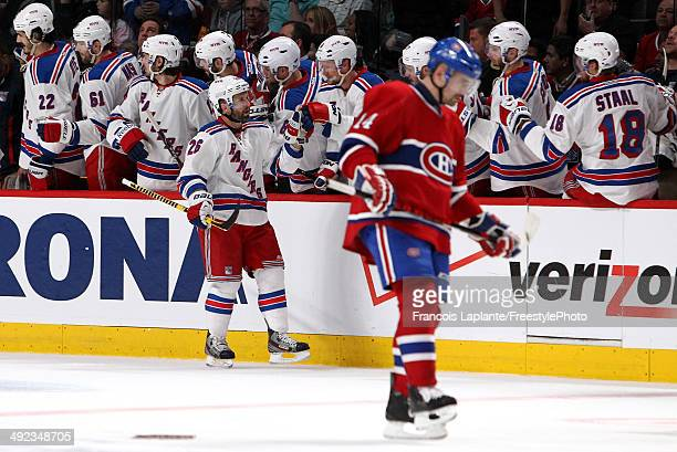 Martin St Louis of the New York Rangers celebrates with his teammates on the bench after scoring a goal against Dustin Tokarski of the Montreal...