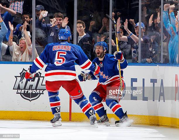 Martin St Louis of the New York Rangers celebrates with teammate Dan Girardi after scoring in the overtime period of Game Four of the Eastern...