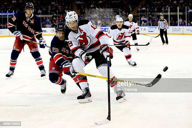 Martin St Louis of the New York Rangers knocks the puck away from Travis Zajac of the New Jersey Devils in the first period during a game at Madison...