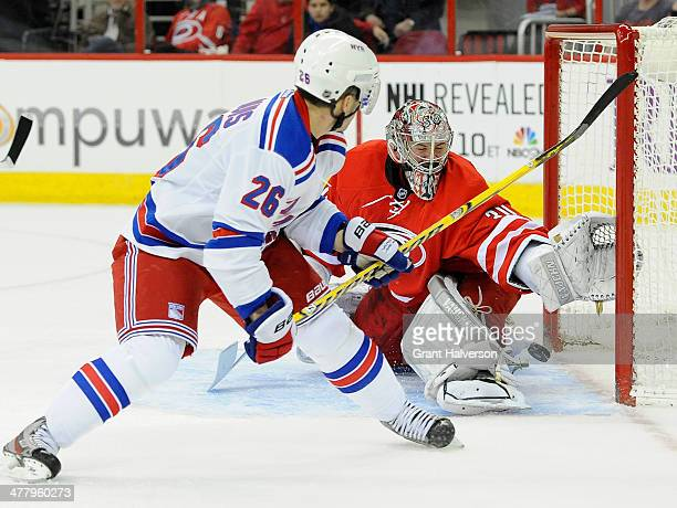 Martin St Louis of the New York Rangers shoots against Cam Ward of the Carolina Hurricanes during a game at PNC Arena on March 11 2014 in Raleigh...