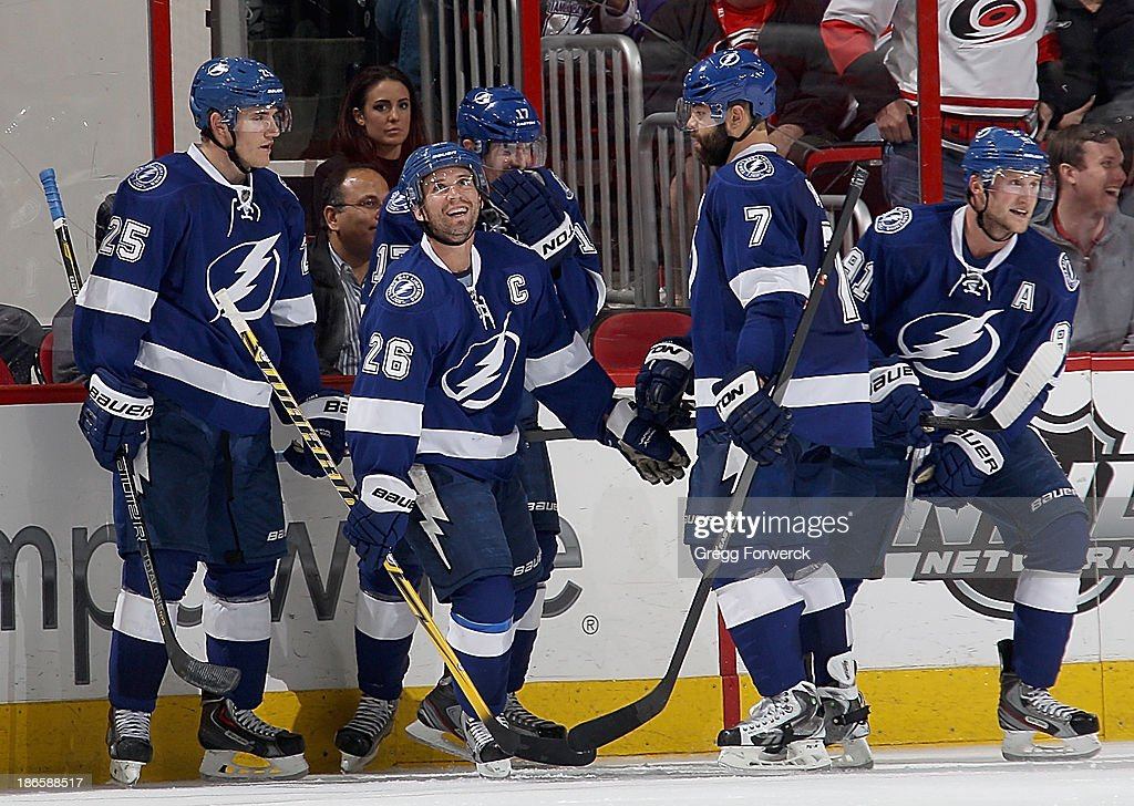 Martin St. Louis #26 of the Tampa Bay Lightning celebrates a late game goal with teammates during their NHL game against the Carolina Hurricanes at PNC Arena on November 1, 2013 in Raleigh, North Carolina.