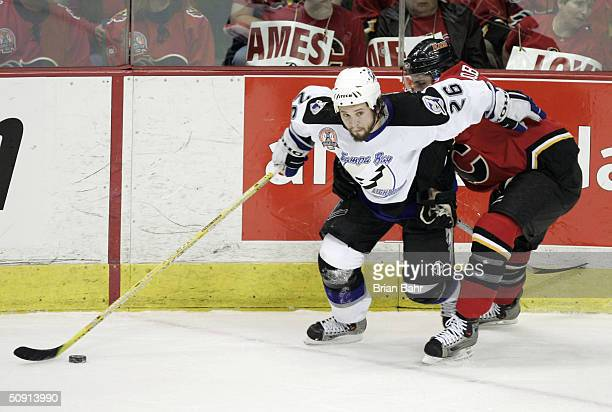 Martin St Louis of the Tampa Bay Lightning gets around Chuck Kobasew of the Calgary Flames in game four of the NHL Stanley Cup Finals on May 31 2004...
