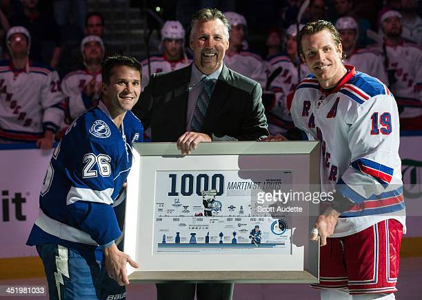 Martin St Louis of the Tampa Bay Lightning is presented with a commemorative plaque celebrating his 1000th NHL game from former teammates Dave...