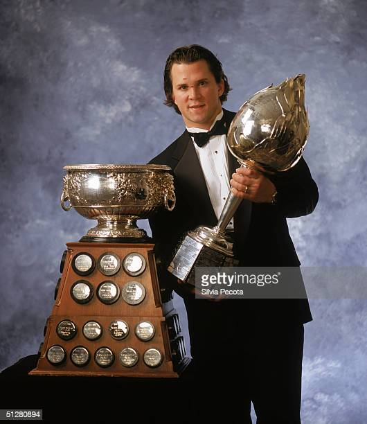 Martin St Louis of the Tampa Bay Lightning poses with the Art Ross Trophy and the Hart Memorial Trophy during the 2004 NHL Awards at the Convention...