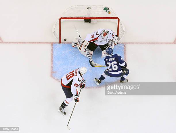 Martin St Louis of the Tampa Bay Lightning scores goal past defenseman Troy Brouwer and goaltender Braden Holtby of the Washington Capitals during...