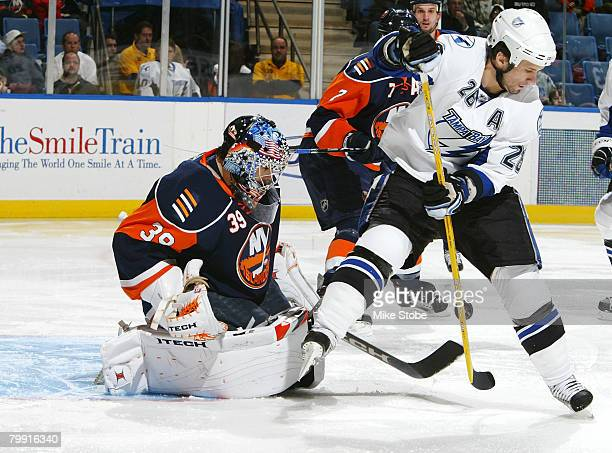 Martin St Louis of the Tampa Bay Lightning tries to slip the puck between his legs as goaltender Rick DiPietro of the New York Islanders defends on...