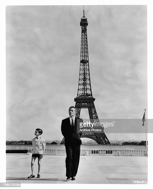 Martin Stephens as Rossano Brazzi's son strike a similar pose before the Eiffel Tower in a scene from the film 'Count Your Blessings' 1958