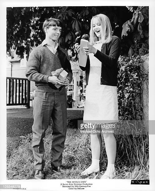 Martin Stephens gives gift of dolls to Ingrid Brett in a scene from the film 'The Devil's Own' 1966