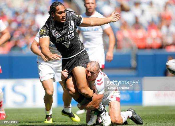 Martin Taupau of New Zealand tosses the ball to a teammate as he's tackled by James Roby of England during the second half of a Rugby League Test...