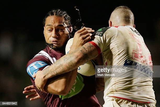 Martin Taupau of the Sea Eagles is tackled by Joel Thompson of the Dragons during the round 17 NRL match between the Manly Sea Eagles and the St...