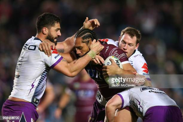 Martin Taupau of the Sea Eagles is tackled during the round 18 NRL match between the Manly Sea Eagles and the Melbourne Storm at Lottoland on July 14...