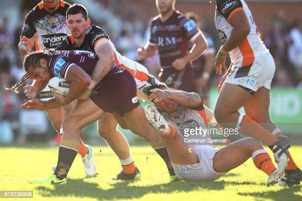 Martin Taupau of the Sea Eagles is tackled during the round 19 NRL match between the Manly Sea Eagles and the Wests Tigers at Lottoland on July 16...
