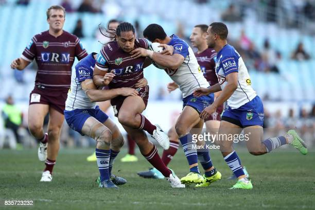 Martin Taupau of the Sea Eagles is tackled during the round 24 NRL match between the Canterbury Bulldogs and the Manly Sea Eagles at ANZ Stadium on...