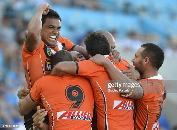 Martin Taupau of the Tigers celebrates with team mates after scoring a try during the round two NRL match between the Gold Coast Titans and the Wests...
