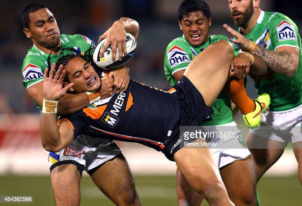 Martin Taupau of the Tigers is tackled by Bill Tupou and Anthony Milford of the Raiders during the round 25 NRL match between the Canberra Raiders...