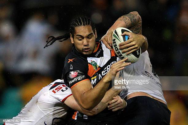 Martin Taupau of the Tigers is tackled during the round 23 NRL match between the Wests Tigers and the Sydney Roosters at Leichhardt Oval on August 16...