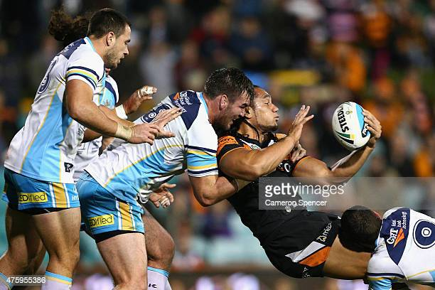 Martin Taupau of the Tigers offloads the ball in a tackle during the round 13 NRL match between the Wests Tigers and the Gold Coast Titans at...